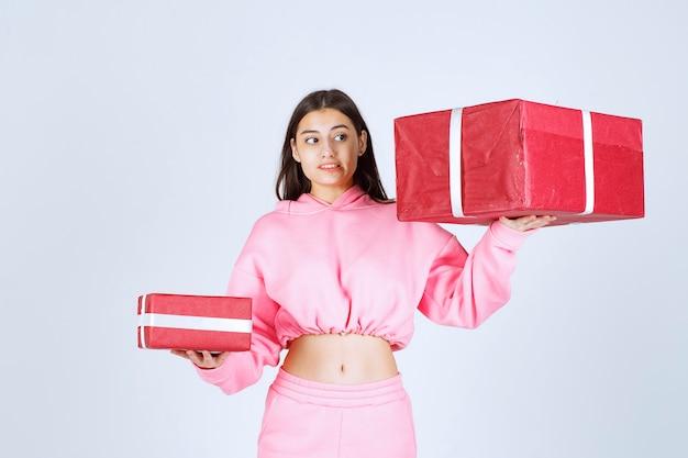 Ragazza in pigiama rosa che tiene scatole regalo rosse grandi e piccole e sembra insoddisfatta.