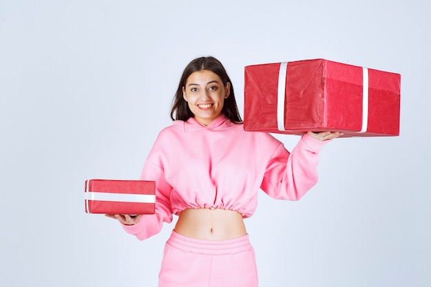 Girl in pink pajamas holding big and small red gift boxes and smiling.