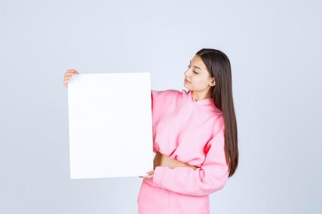 Ragazza in pigiama rosa che tiene una scheda di presentazione quadrata vuota di un nuovo progetto.