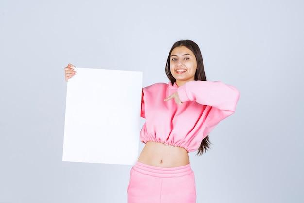 Ragazza in pigiama rosa che tiene una scheda di presentazione quadrata vuota e indicandola.