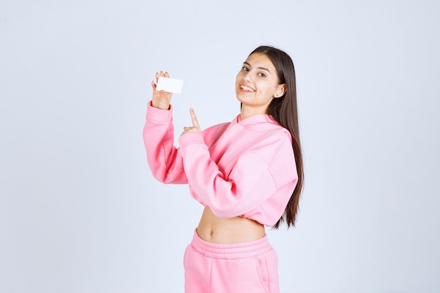 Girl in pink pajamas holding a business card and introducing herself to her business partners.