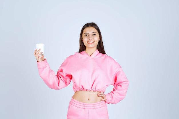 Ragazza in pigiama rosa che tiene una tazza di caffè e che indica qualcosa