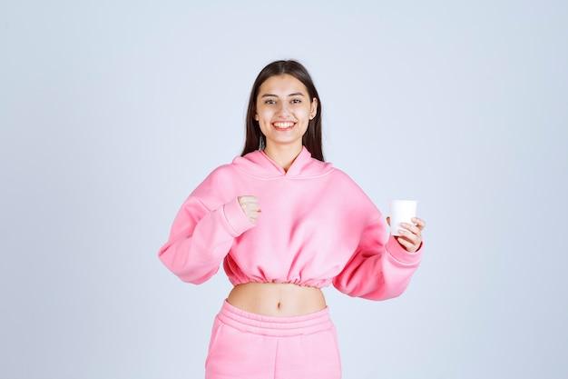 Ragazza in pigiama rosa che tiene una tazza di caffè e che mostra il suo pugno