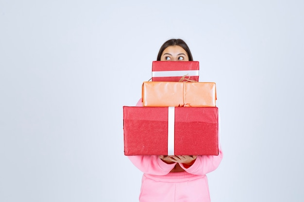 Girl in pink pajamas holding multiple red gift boxes and hiding her face behind them.