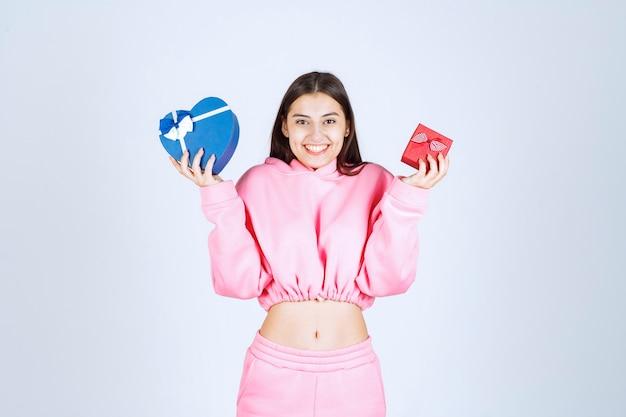 Ragazza in pigiama rosa che tiene scatole regalo a forma di cuore rosso e blu in entrambe le mani.