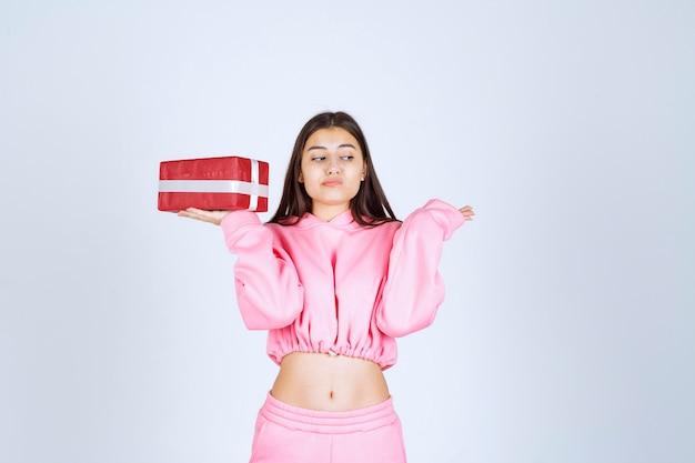 Ragazza in pigiama rosa che tiene una scatola regalo rettangolare rossa e sembra indifferente.