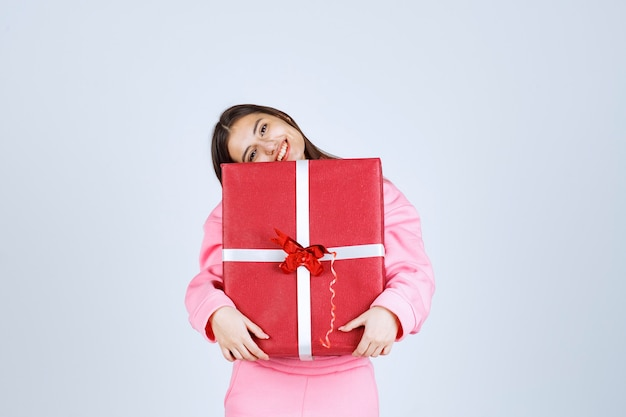 Ragazza in pigiama rosa che abbraccia una grande confezione regalo rossa e sorridente.