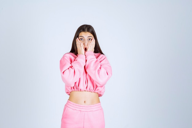 Girl in pink pajamas looks scared and frightened