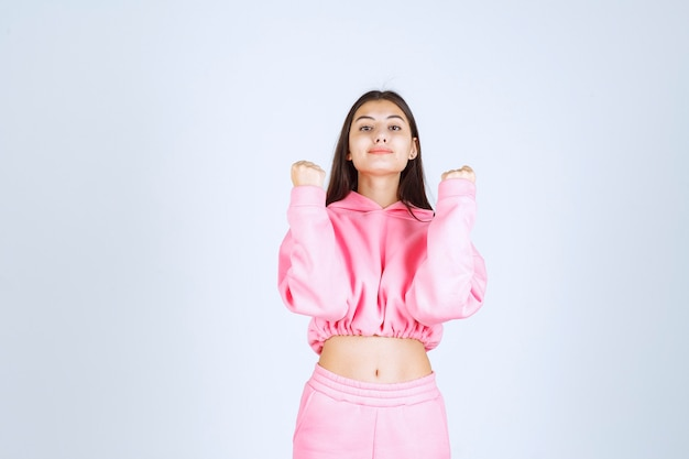 Girl in pink pajamas looks sportive and shows her fists