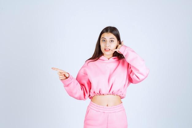 Ragazza in pigiama rosa che fa il segnale di chiamata