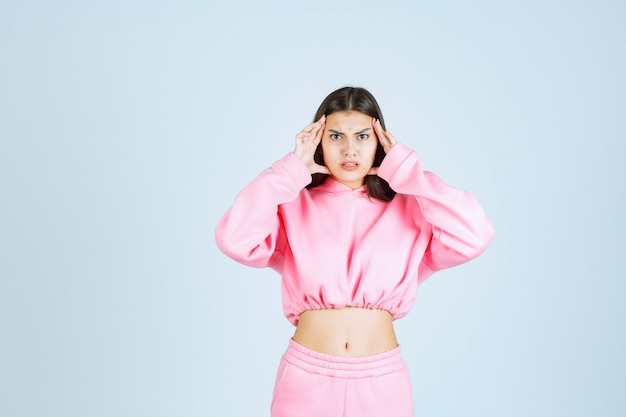 Girl in pink pajamas making very agressive and angry face
