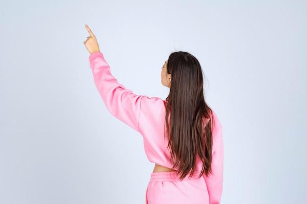 Girl in pink pajamas pointing backward