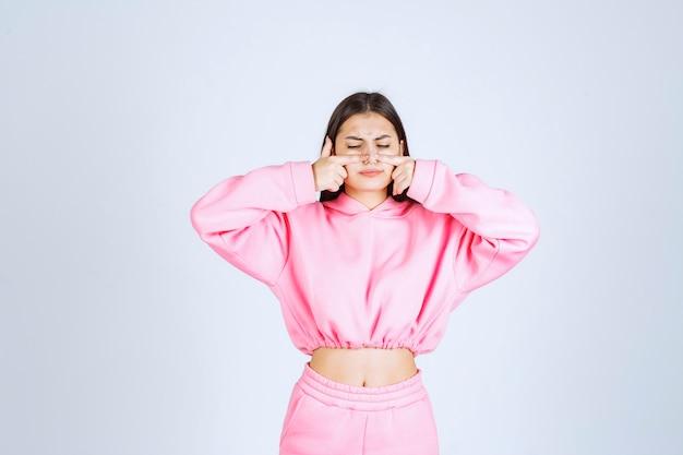 Ragazza in pigiama rosa che punta alla bocca