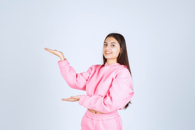 Girl in pink pajamas pointing at something on the left