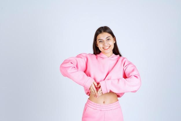 Girl in pink pajamas sending love
