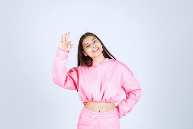 Ragazza in pigiama rosa che mostra il segno di godimento