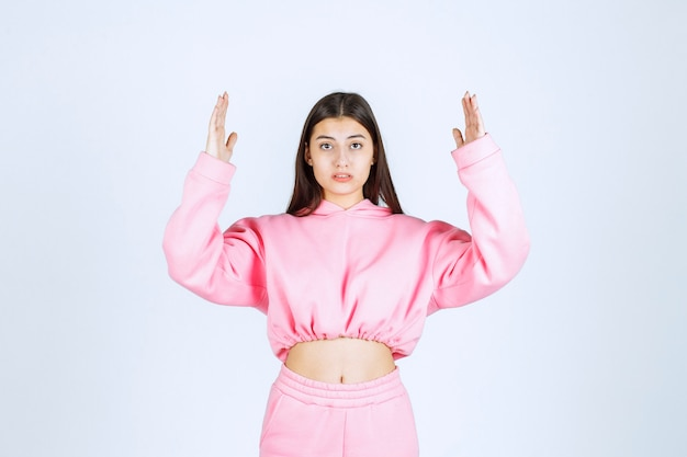Girl in pink pajamas showing the estimated amount or size of a product