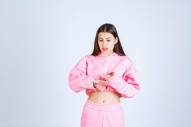 Ragazza in pigiama rosa che mostra le dimensioni di un oggetto
