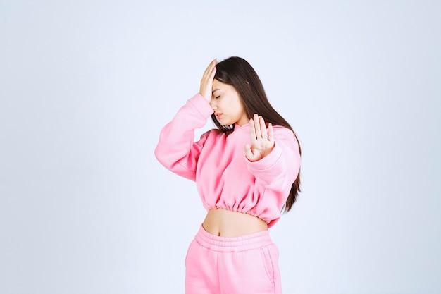 Girl in pink pajamas stopping something or somebody