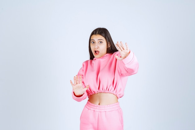 Girl in pink pajamas stopping something