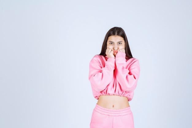 Ragazza in pigiama rosa sorpresa e scioccata