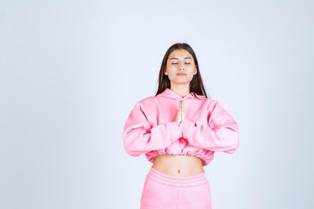 Ragazza in pigiama rosa che unisce le sue mani e che prega