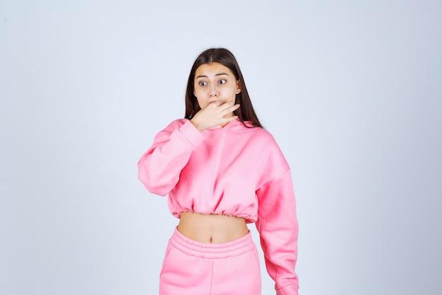Ragazza in pigiama rosa che fischia