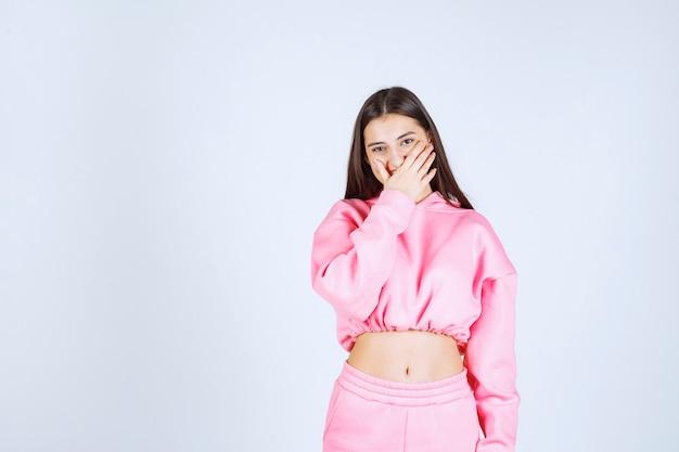 Ragazza in pigiama rosa, guardando attraverso le dita