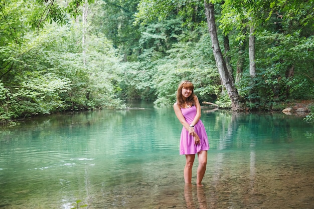 Girl in a pink short dress walks on a river in the forest