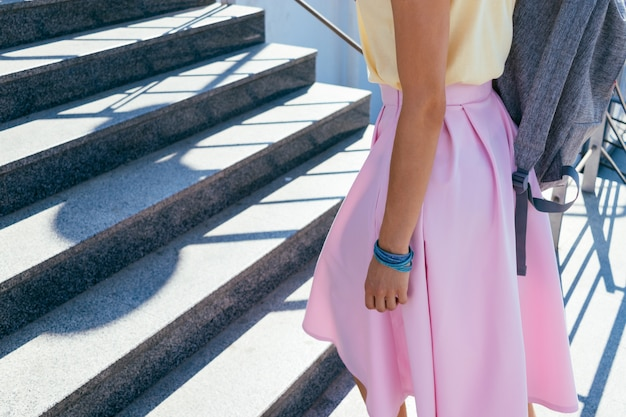 Girl in a pink skirt and yellow t-shirt climbing stairs outdoors