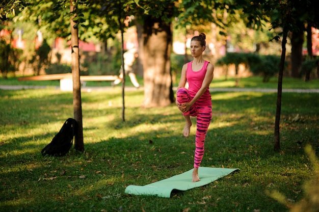 Girl in the pink sportsuit practicing yoga in the park
