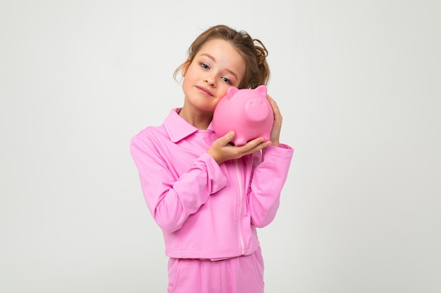 Girl in a pink suit holding a piggy bank on a white wall with blank space