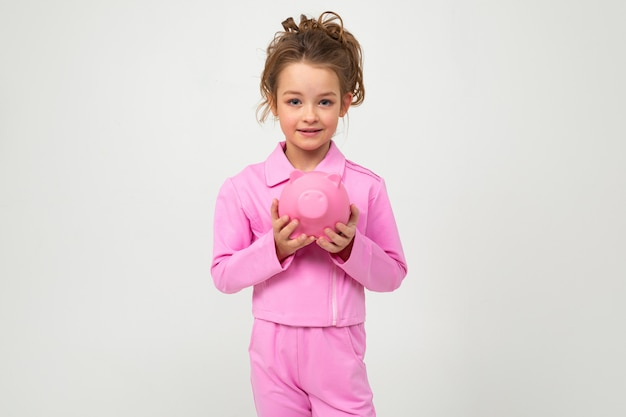 Girl in a pink suit holds a piggy bank on a white wall with blank space