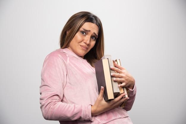 Ragazza in swaetshirt rosa che tiene e che trasporta pile pesanti di libri.