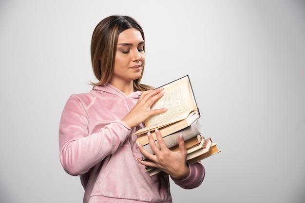 Ragazza in swaetshirt rosa che tiene una scorta di libri, aprendone uno in alto e leggendolo.