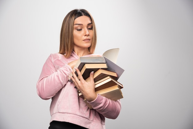 Ragazza in swaetshirt rosa che tiene una scorta di libri, aprendone uno in alto e leggendolo