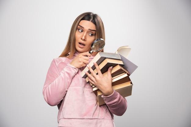 Ragazza in swaetshirt rosa che tiene una scorta di libri e cerca di leggere quello in alto con una lente d'ingrandimento.
