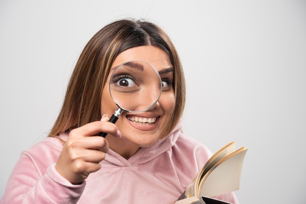 Ragazza in swaetshirt rosa che si mette una lente d'ingrandimento per gli occhi e guarda attraverso di essa.