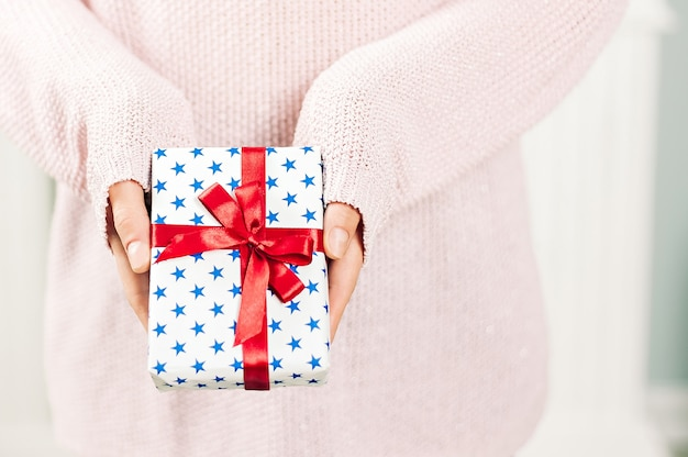 A girl in a pink sweater, holds in her hands a gift with blue stars and a red ribbon. on a light background. concept on the theme of holidays.
