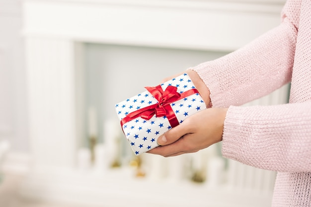 A girl in a pink sweater, holds in her hands a gift with blue stars and a red ribbon. on a light background.