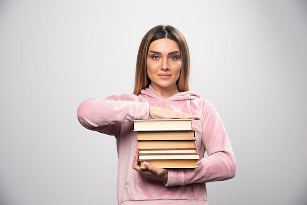 Ragazza in felpa rosa che tiene e che trasportano pesanti pile di libri.