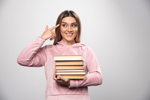 Ragazza in felpa rosa che tiene una scorta di libri e si sente intelligente.