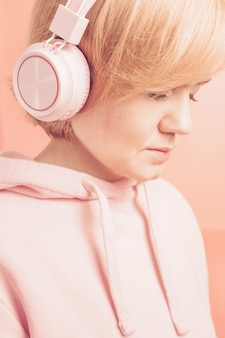 Girl in a pink sweatshirt and with pink headphones on a background similar in tone