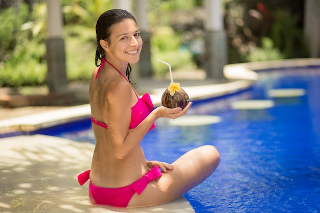The girl in the pink swimsuit is resting on the edge of the pool with a drink from a coconut