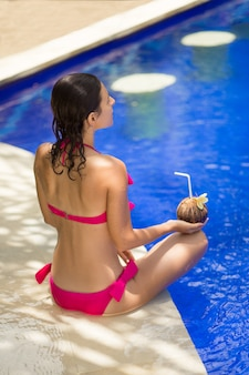 The girl in the pink swimsuit is resting on the edge of the pool with a drink from a coconut.