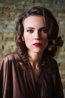 ブルネットの髪と暗い背景にバスローブで赤い唇とレトロなメイクの女の子のピンナップ。ベッドに座っている女の子。ヴィンテージ画像。