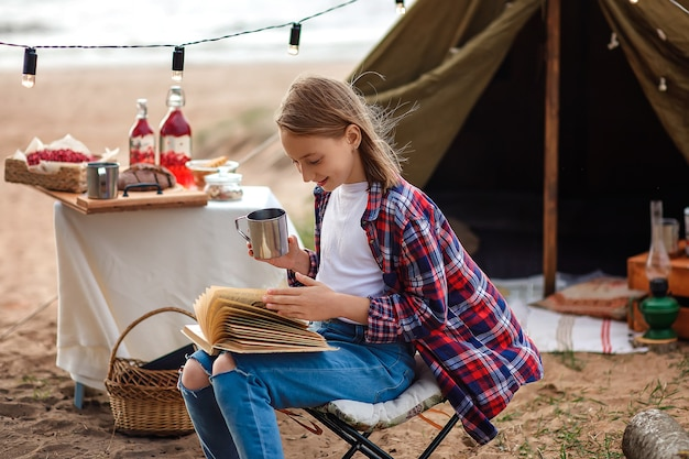 A girl in a plaid shirt reads a book against the background of a tent and a lake.