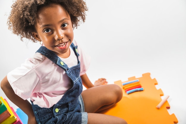 Girl on play mat with plasticine in studio