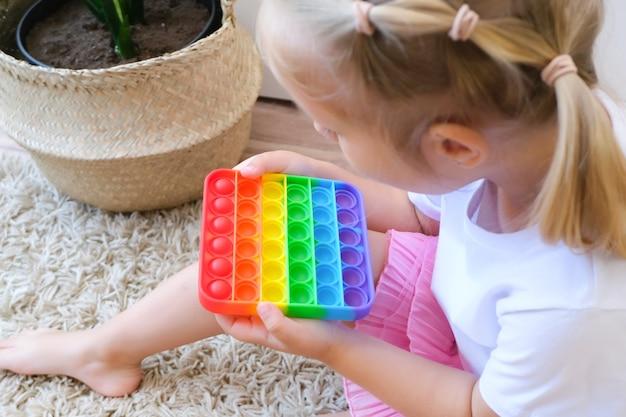 소녀는 감각 장난감을 팝니다. 스트레스와 불안 완화. 스트레스 받는 아이들을 위한 트렌디한 실리콘 손놀림 게임
