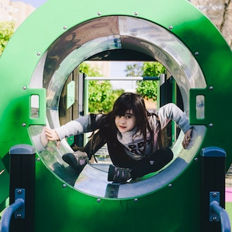 Girl in playground tube
